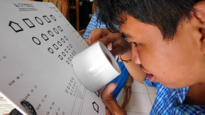 A child with a hearing impairment undergoes a low vision assessment in Cambodia.